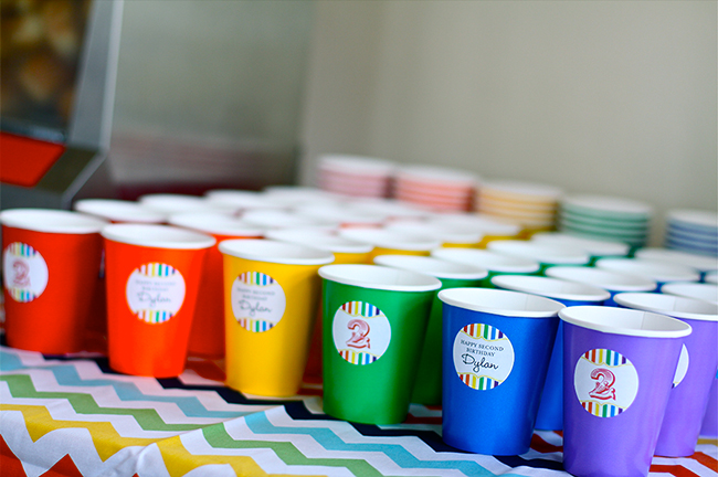 A gorgeous rainbow birthday party! - Colored paper cups with personalized stickers from Chickabug