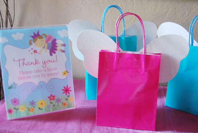 Garden fairy theme birthday party favors - bags with fairy wings & a DIY sign from Chickabug