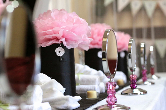 Spa theme birthday party decor - pink flower centerpieces and a make-up mirrors