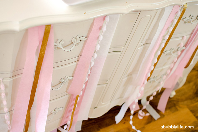 Dress-up theme birthday party - streamers, glitter tape and pom poms tucked in a dresser