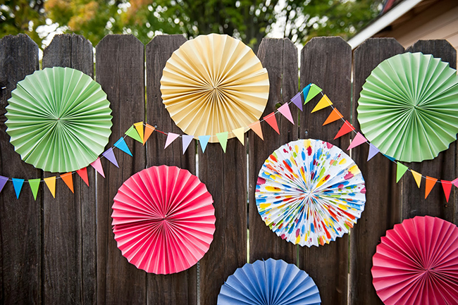 Pop art theme birthday party - rainbow pennant banners and colorful paper rosettes