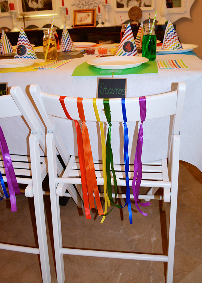 Chalkboard rainbow theme birthday party - White chairs decorated with rainbow ribbons